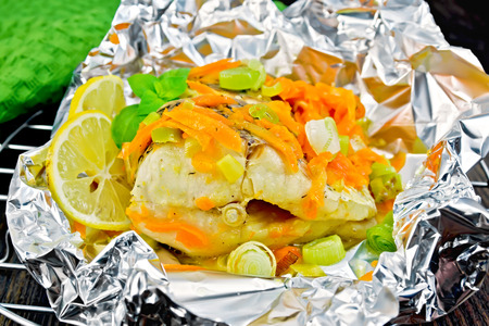 limnetic: Pike with carrots, leek, basil and lemon slices in a foil on a metal grid, towel on a dark wooden board