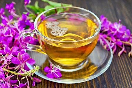 Herbal tea in a glass cup, fresh flowers fireweed against the dark wooden board