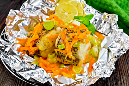 limnetic: Pike with carrots, leek, basil and lemon slices on the grill in foil, a green towel on a wooden boards background
