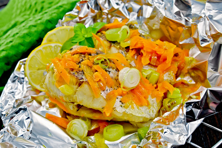 limnetic: Pike with carrots, leek, basil and lemon slices in a foil on a metal grid, green towel on the background of wooden boards