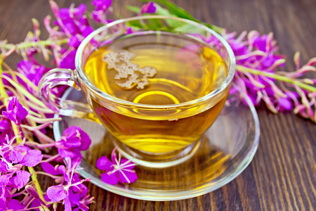 fireweed: Herbal tea in a glass cup and fresh flowers fireweed against the backdrop of wooden planks