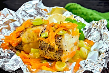 limnetic: Pike with carrots, leeks, basil and lemon slices in a foil, a towel on the background of wooden boards