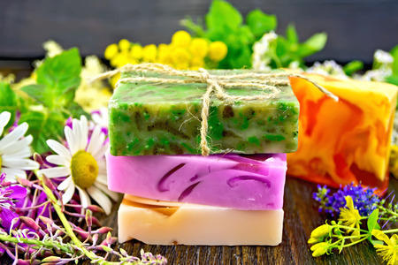 milfoil: Three multi-colored bar of homemade soap, fireweed flowers, tansy, chamomile, clover, yarrow, tutsan and meadowsweet, mint and lemon balm leaves on the background of wooden boards Stock Photo