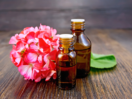 Two bottle of oil with green leaf and flower of pink geranium on a wooden boards background Standard-Bild