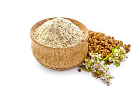 harina: harina de trigo sarraceno en un tazón de madera, trigo sarraceno, alforfón flor aislada en el fondo blanco