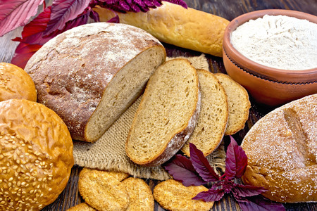 amaranthus: Bread, rolls and biscuits, amaranth flour in a clay bowl, purple amaranth flower on the background of wooden boards Stock Photo