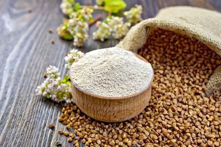 La farine de sarrasin dans un bol en bois, le sarrasin dans le sac, le sarrasin fleur sur le fond des planches de bois