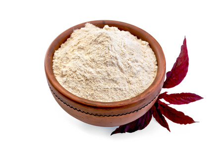 Amaranth flour in a clay bowl and purple amaranth flower isolated on white background