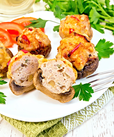 farce: Mushrooms stuffed with meat whole and sliced parsley and tomatoes in a white plate on a towel, fork on a wooden boards background