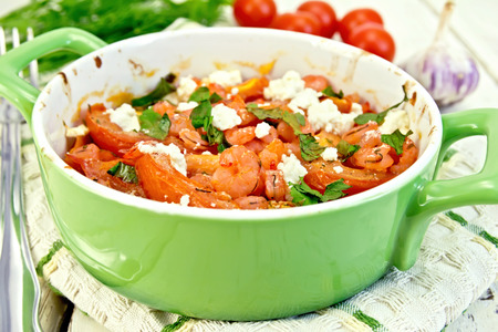 roasting pan: Shrimp and tomatoes baked with feta cheese in a roasting pan on a kitchen towel, parsley and garlic on a wooden boards background Stock Photo