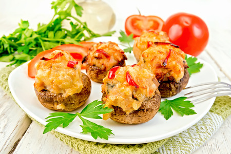 farce: Mushrooms stuffed with meat with parsley and tomatoes in a white plate on a towel, fork on a wooden boards background Stock Photo