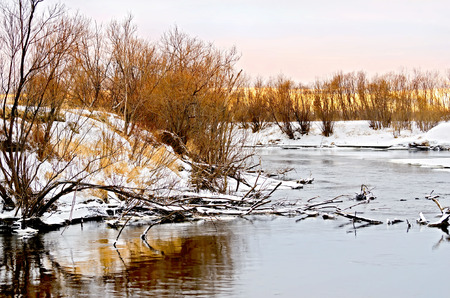 frozen winter: Flowing water and snow-covered trees on the shore with sunset sky background Stock Photo