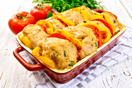 roasting pan: Cutlets of turkey meat baked with tomatoes and yellow pepper in a ceramic roasting pan on a towel, parsley on a wooden boards background