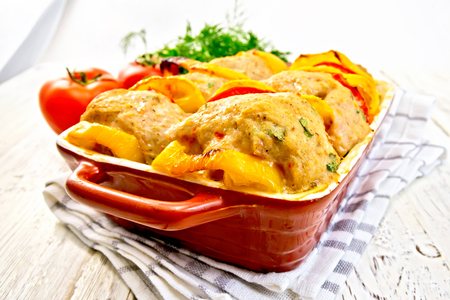 roasting pan: Cutlets of turkey meat baked with red tomatoes and yellow pepper in a ceramic roasting pan.