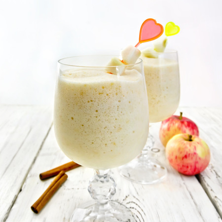airy: Jelly airy apple in wineglasses, red apples and cinnamon on a background of bright wooden boards