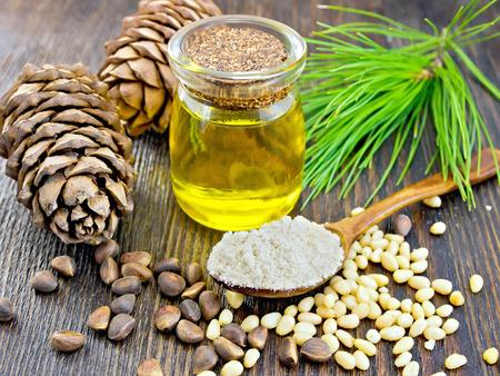pine kernels: Cedar Flour in a wooden spoon, cedar nuts and  two cones, cedar oil in a glass jar, a cedar branch against the backdrop of wooden planks