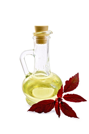decanter: Decanter with vegetable oil and a sprig of maroon amaranth isolated on white background