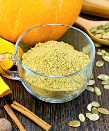 dried gourd: Flour pumpkin in a glass cup, rolling pin, spoon, nutmeg and cinnamon, fresh pumpkin, pumpkin seeds on the background of wooden boards Stock Photo