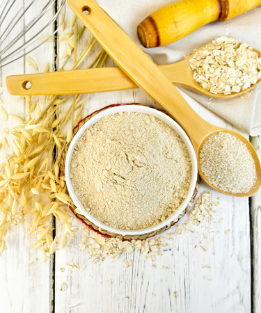 harina: Oat flour in white bowl, oatmeal and bran in wooden spoon, stalks of oats on the background of the wooden planks on top