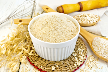 Oat flour in white bowl, oatmeal and bran in wooden spoon, stalks of oats on the background of wooden boards
