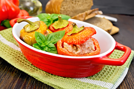 roasting pan: Three sweet peppers stuffed with meat and rice with basil leaves in red roasting pan on a green napkin, bread on a dark wooden board