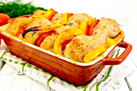 roasting pan: Cutlets of turkey meat baked with red tomatoes and yellow pepper in a ceramic roasting pan on a towel, parsley on a wooden boards background