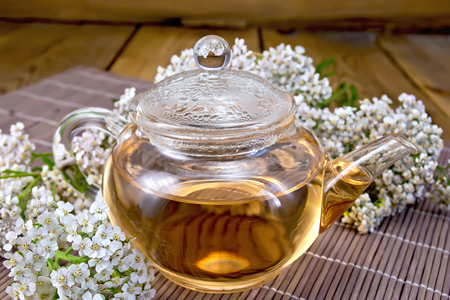 milfoil: Tea with yarrow in a glass teapot, fresh flowers, yarrow on background of bamboo towels and wooden boards