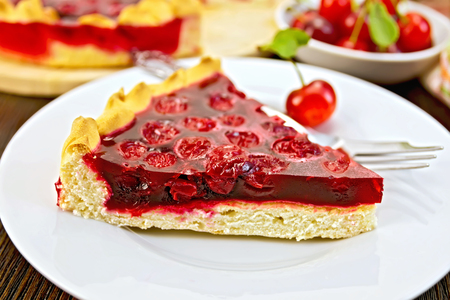 jam tarts: Piece of sweet pie with cherries and jelly in a white plate with a fork on the background of wooden boards