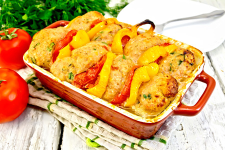 roasting pan: Cutlets of turkey meat baked with tomatoes and yellow pepper in a ceramic roasting pan on a kitchen towel, parsley on the background light wooden boards