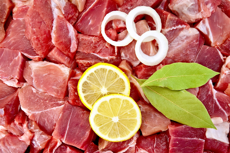 pulpy: Texture of pieces of raw meat with bay leaf, rings of white onion and lemon slices Stock Photo