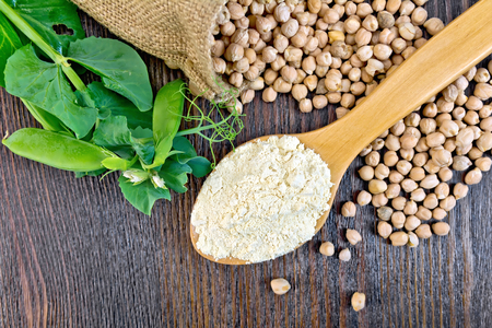 spoonful: Flour chickpeas in spoonful, chick-peas in a sack and fresh pea pods on a background of wooden boards top Stock Photo