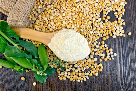 spoon yellow: Flour pea in a spoon, yellow flakes in a bag and fresh pods on a background of wooden boards Stock Photo