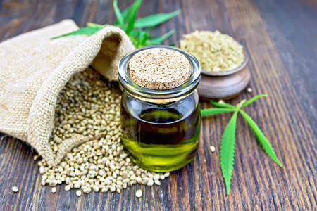 Hemp oil in a glass jar with flour in a clay bowl and grain in a bag, cannabis leaves and stalks on a wooden boards background