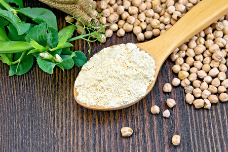 spoonful: Flour chickpeas in spoonful, chick-peas in a sack and fresh pea pods on a background of wooden boards