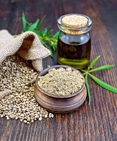 Hemp flour in a clay bowl, the grain in the bag and on the table, the oil in a glass jar, cannabis leaves on the background of wood planks Reklamní fotografie