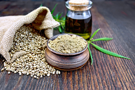 Hemp flour in a clay bowl, the grain in the bag and on the table, the oil in a glass jar, leaves and stalks of cannabis on a background of wooden boards