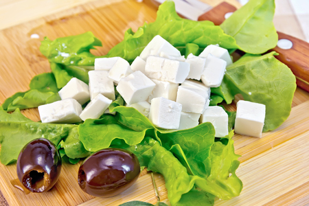 Feta cheese on green lettuce, olives, knife on background wooden board and cloth