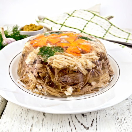 Jellied pork and beef with carrots and parsley on a plate, towel, garlic, mustard and dill on a wooden boards background
