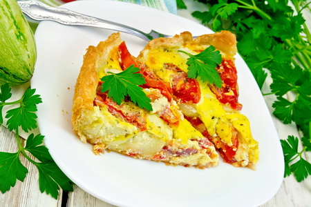 Two pieces pie of zucchini with tomatoes and eggs in a plate on a napkin, parsley on the background light wooden boards Stock Photo