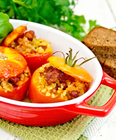 roasting pan: Tomatoes stuffed with meat and steamed wheat bulgur in a roasting pan on a napkin, bread and parsley on a wooden board background