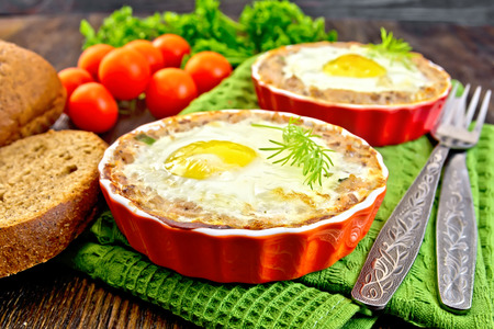 Two forms of tartlets with meat and eggs in the forms on a napkin, tomatoes, bread, parsley and dill on background of wood planks Stock Photo