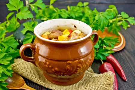 Roast with chicken, potatoes, squash, and sweet peppers in a portion clay pot on a napkin of burlap, spoon, parsley on a wooden table background