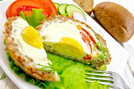 Tartlets meat with egg and tomato cut in the white plate on lettuce, bread and dill on the background light wooden boards