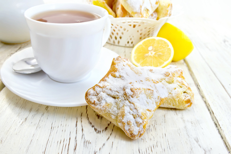 Cookies lemon, tea in a white cup on saucer, lemons on a background of wooden boards