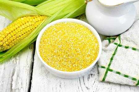 Corn grits in a white bowl, cobs, a jug of milk and a napkin on a wooden boards background