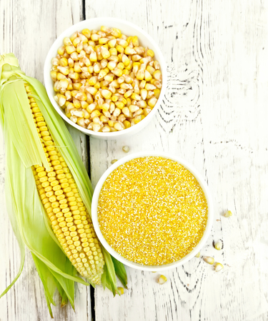 Corn grits and grains in two bowls, cob on the background of the wooden planks on top Stock Photo