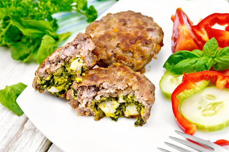 farce: Cutlets stuffed with spinach and egg, salad with tomatoes, cucumber and pepper in a dish on a towel, basil and parsley on the background light wooden boards Stock Photo