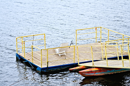 pierce: Pierce with yellow railings and wooden flooring with spinning, white plastic chair on the water