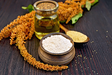 Flour amaranth in a clay bowl, oil in glass jar, a spoon with grain, brown flower with green leaves on a background of wooden boards