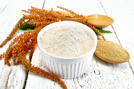 Amaranth flour in white bowl, spoons with grain, brown flower with green leaves on a background of wooden boards